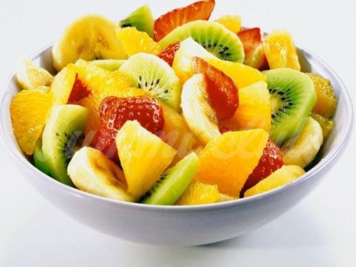 На фото Фруктовый салат с ананасом, киви, бананами, мандаринами и апельсинами