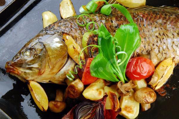 На фото Запеченный карп с овощами
