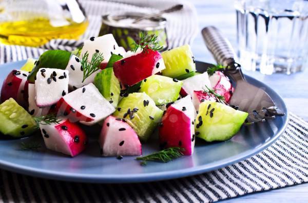 На фото Весенний салат из редиса с огурцами и фетой