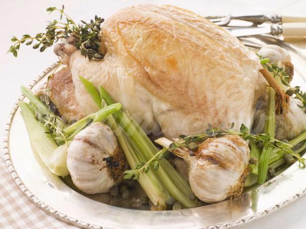 На фото Запеченная курица с чесноком и розмарином