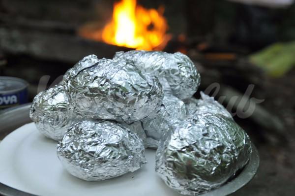 На фото Запеченный картофель в фольге на углях