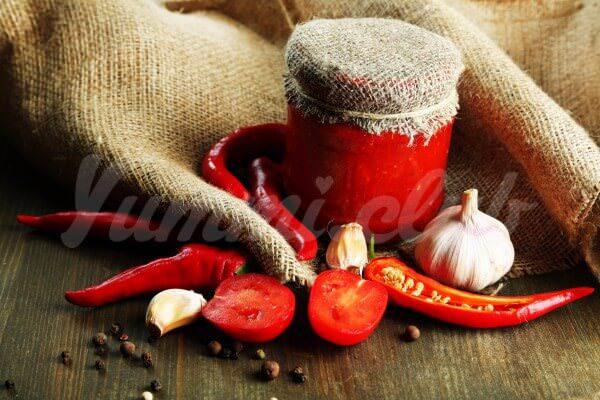 На фото Аджика из помидоров и чеснока