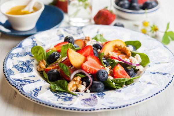 На фото Летний салат из шпината с фруктами и ягодами