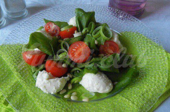 На фото Испанский салат с моцареллой, шпинатом, помидорами и горохом