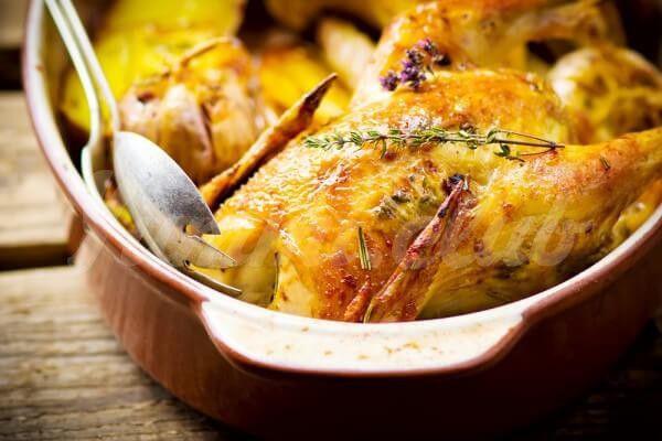 На фото Запеченная курица с картофелем и пряными травами