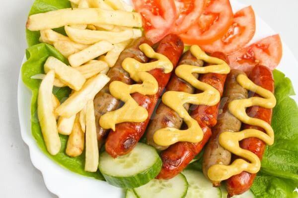 На фото Жареные сосиски с картофелем фри и овощами