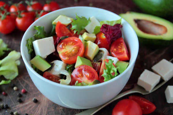 На фото Весенний салат из авокадо, феты и помидоров