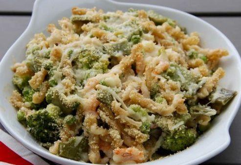 На фото Запеченная паста с креветками, зелеными овощами и ароматным сыром