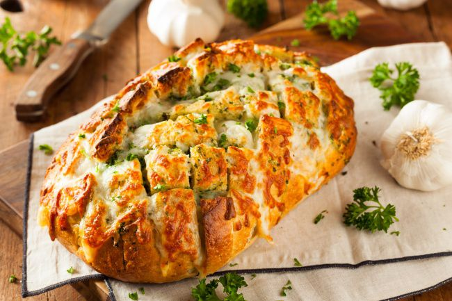 На фото Черный хлеб с сыром, запеченный в духовке