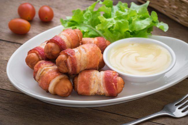 На фото Закуска-рулет в духовке из сосисок и бекона (быстро и вкусно)