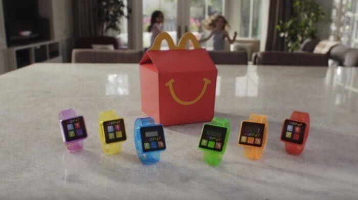 На фото McDonald's вкладывает фитнес-трекеры в Happy Meal
